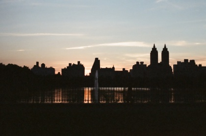 The Jacqueline Kennedy Onassis Reservoir and its surrounding buildings on a summer evening.